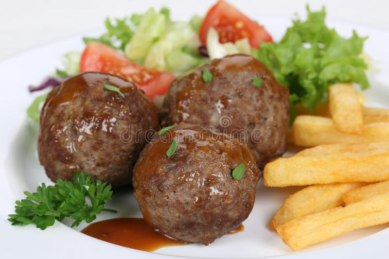 Meatballs meal with french fries and lettuce. On plate stock photos