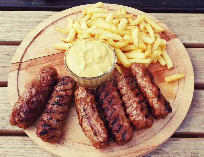 Meatballs meat french fries mutard plate sausages romanian mici royalty free stock images