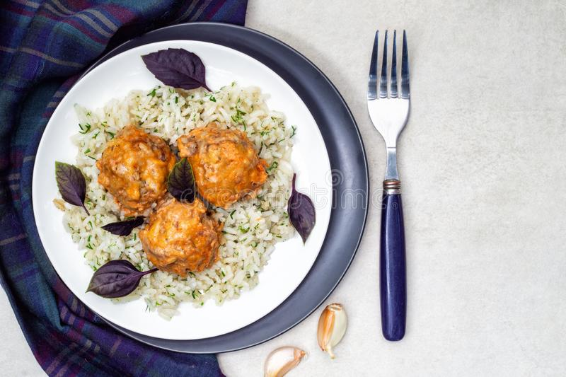 Meatballs and rice in a white and black plates with herbs and basil. Top view royalty free stock photos