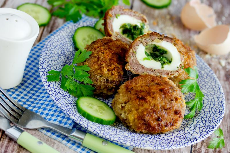 Meatballs stuffed with boiled eggs and green herbs butter. In bread crumbs royalty free stock photos