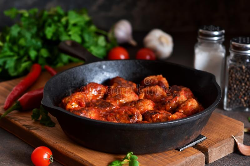 Meatballs in sweet and sour tomato sauce on the kitchen table. Top view royalty free stock images