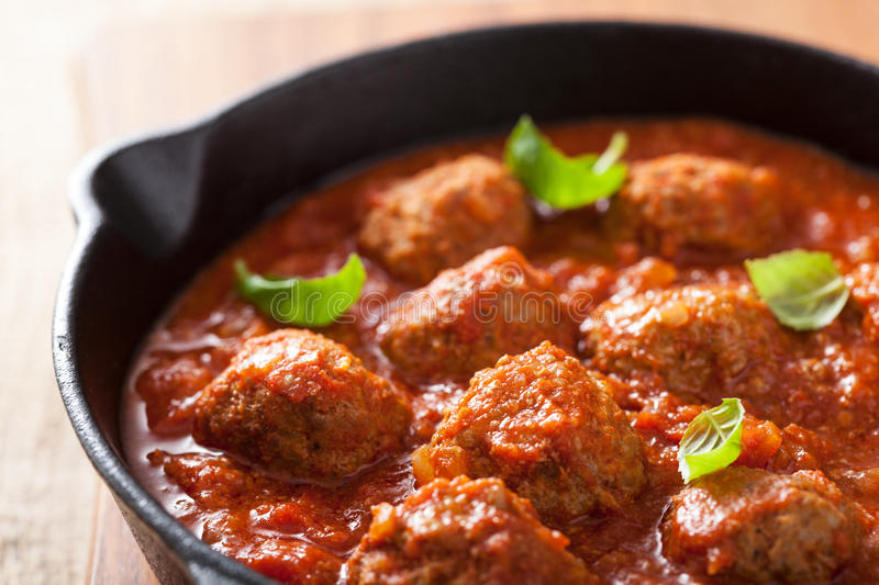 Meatballs with tomato sauce in black pan stock photo