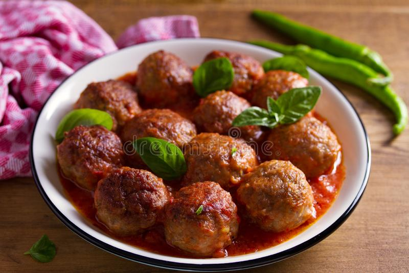 Meatballs in tomato sauce, garnished with basil in bowl on wooden table. royalty free stock images