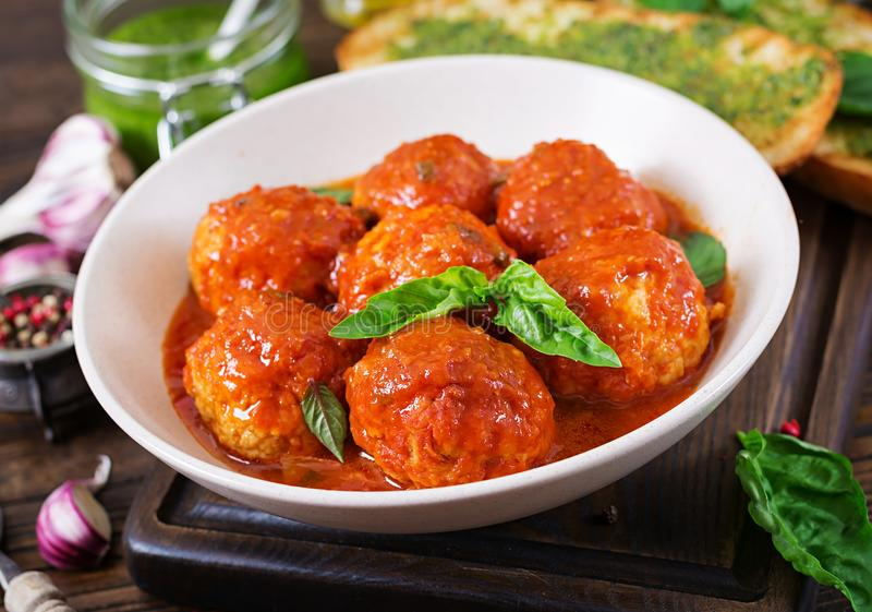 Meatballs in tomato sauce and toast with basil pesto. Dinner. stock photo