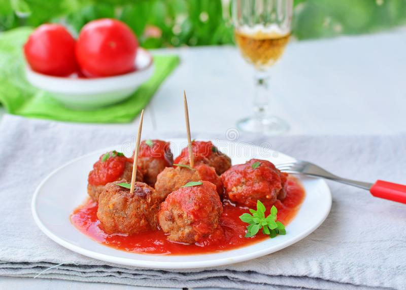 Meatballs in tomato sauce on white plate with greek basil stock photo