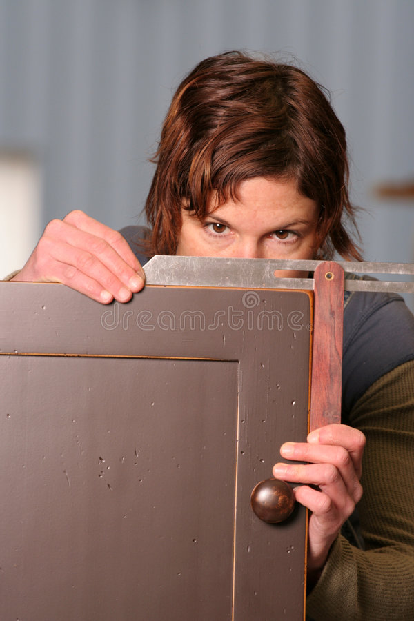 Meausre Once. A woodworker measure a cabinet door for square stock photography