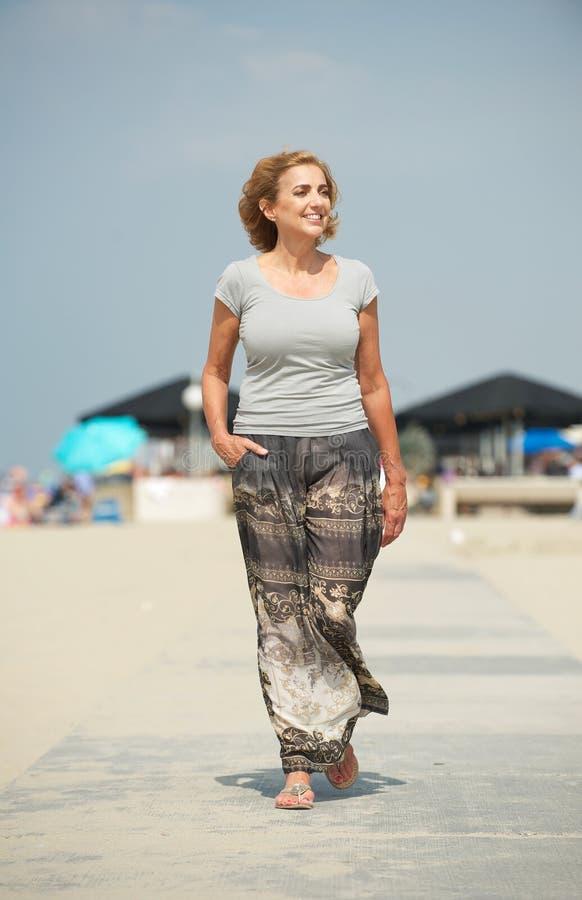 Meautiful oudere vrouw die bij het strand lopen stock foto