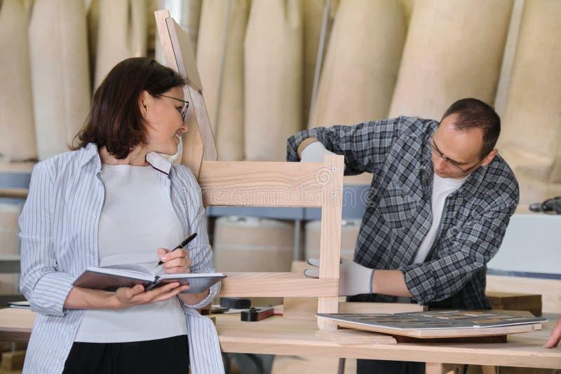 Meblarska joinery produkcja, pracuj?cy m?ski joiner i kobiety w?a?ciciel biznesu z notatnikiem, zdjęcia royalty free