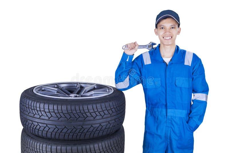 Mecánico alegre con los neumáticos y la llave fotografía de archivo libre de regalías