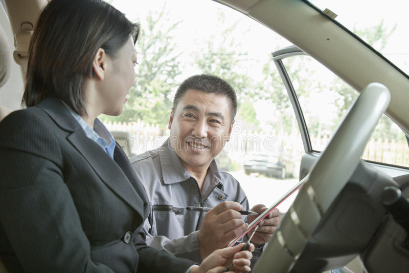 Mecánico alegre Explaining a la empresaria y mostrarle la cuenta fotografía de archivo libre de regalías