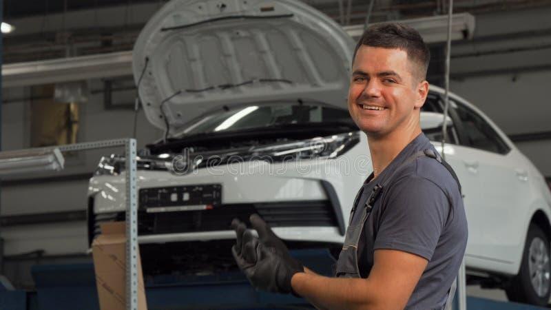 Mecánico alegre que pone en sus guantes que sonríen a la cámara fotografía de archivo libre de regalías