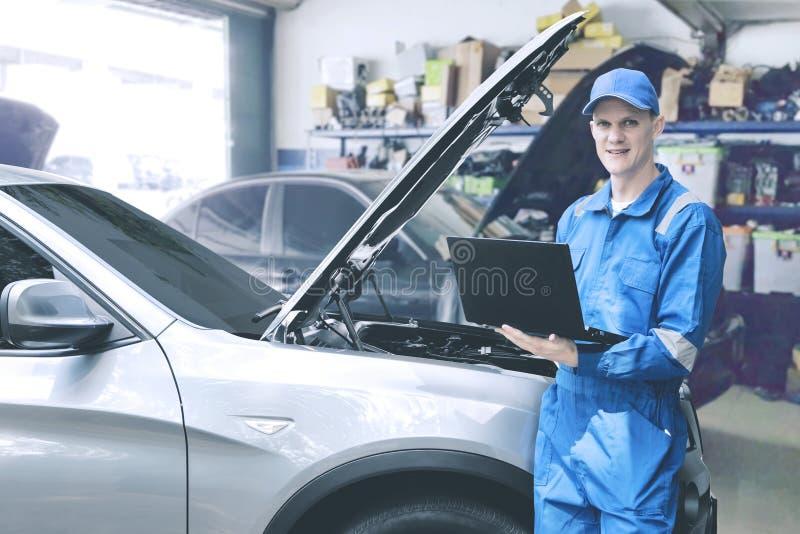 Mecánico caucásico que comprueba el motor de coche usando el ordenador portátil del ordenador en el taller de reparaciones fotos de archivo