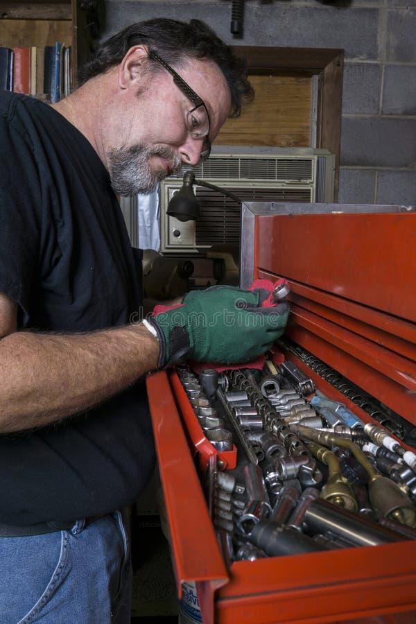 Mecánico Cleaning una llave foto de archivo libre de regalías