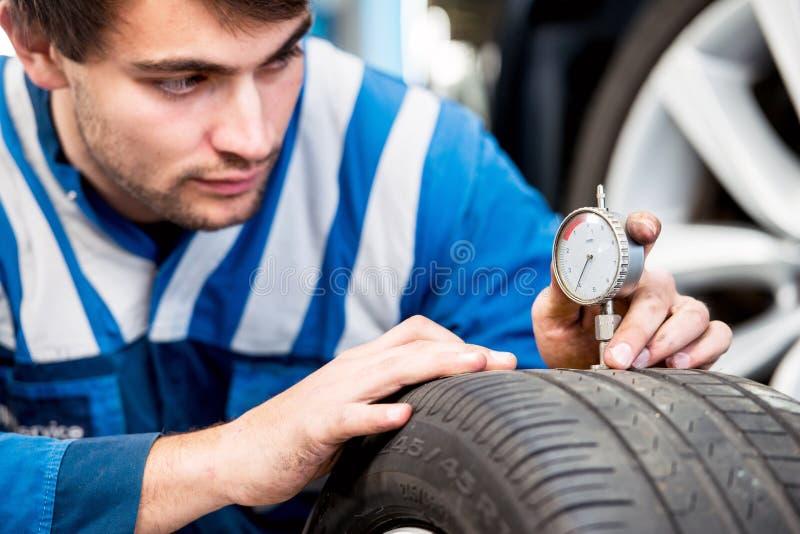 Mecánico, comprobando el desgaste en la pisada de un neumático fotos de archivo