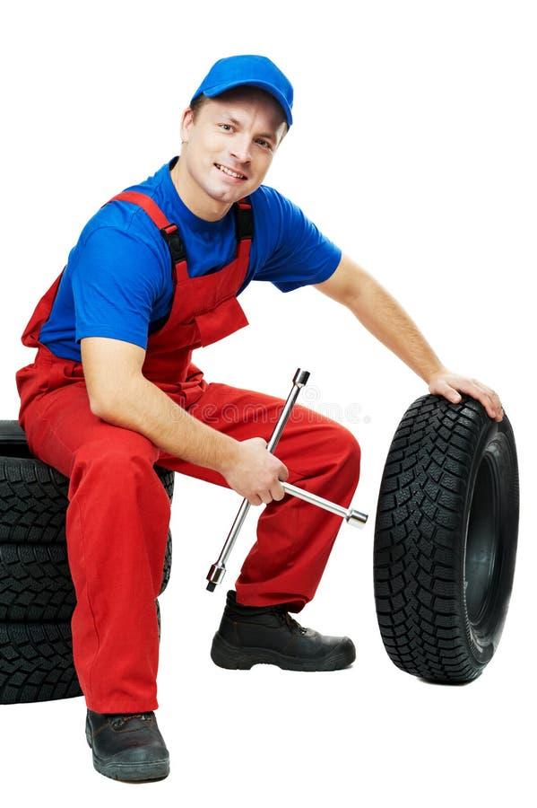 Mecánico de automóvil con el neumático y la llave inglesa de coche fotografía de archivo