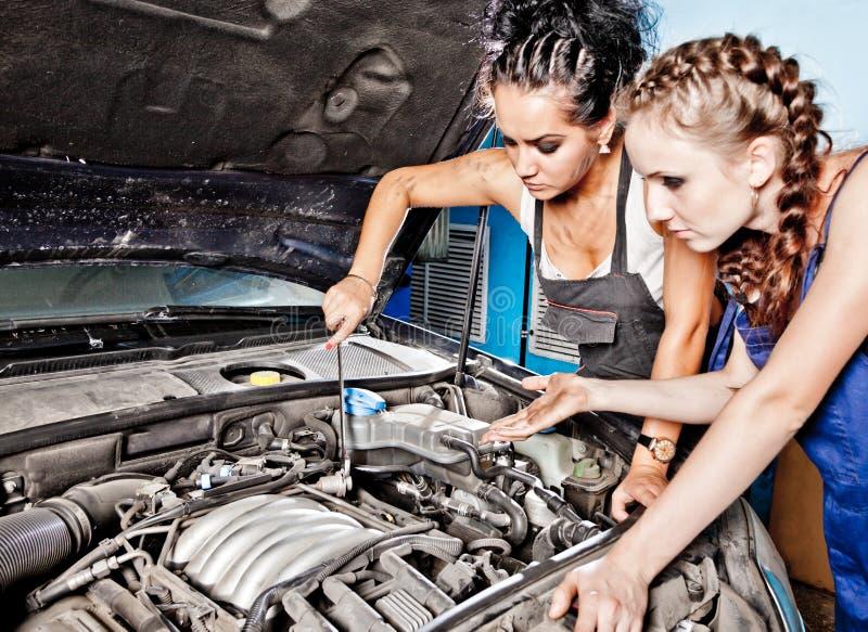 Mecánico de automóviles de dos hembras que repara un coche fotografía de archivo libre de regalías