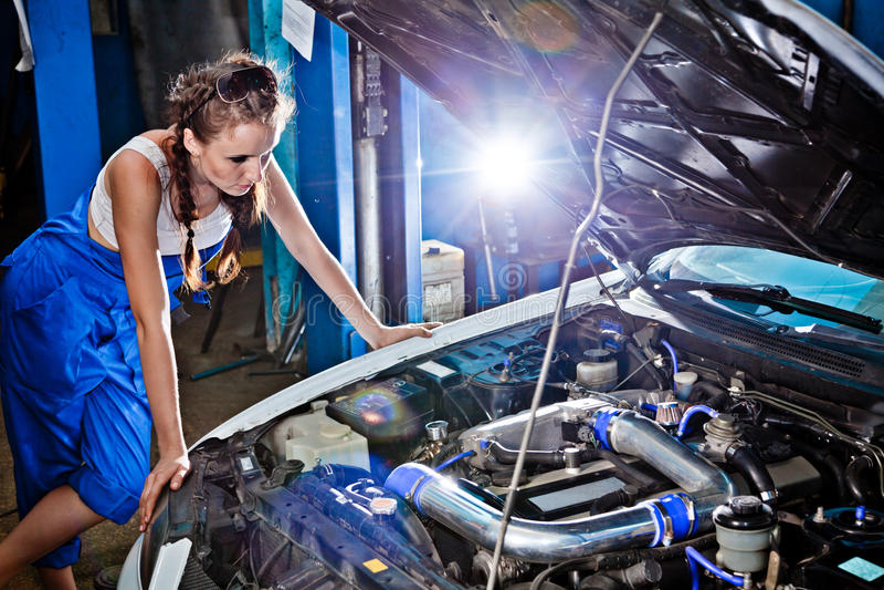 Mecánico de automóviles de sexo femenino que repara un coche foto de archivo