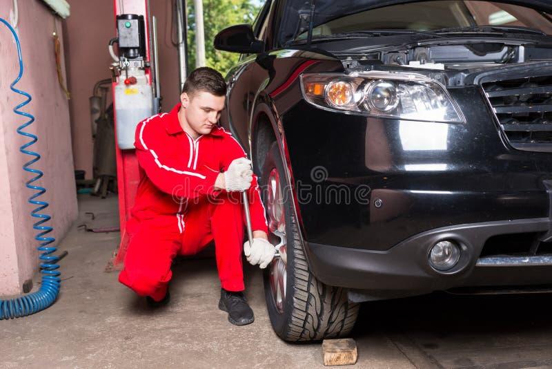 Mecánico de automóviles de sexo masculino que atornilla o que desatornilla la rueda de coche por la llave fotografía de archivo libre de regalías