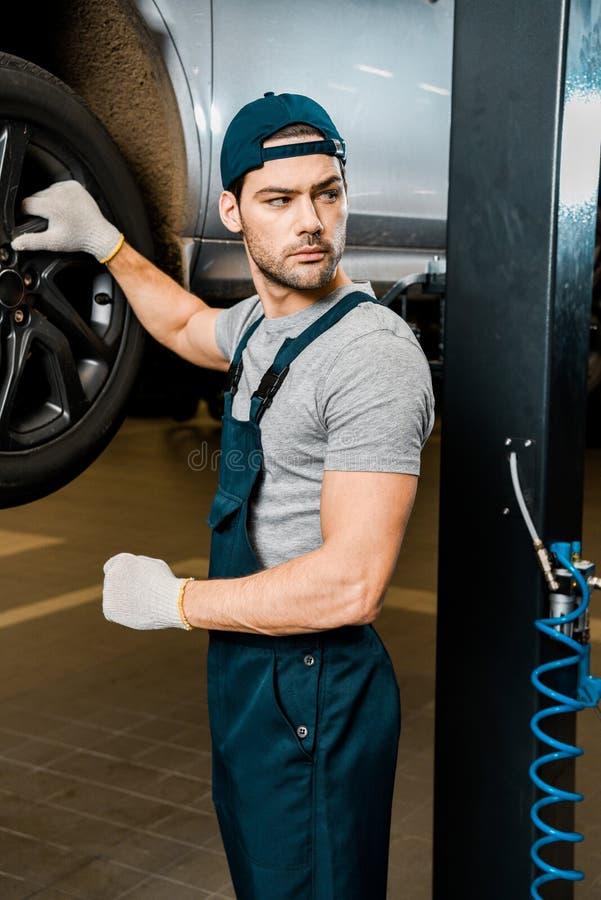 mecánico de automóviles joven en los guantes protectores que se colocan en el automóvil fotografía de archivo