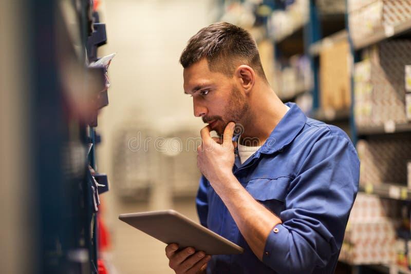Mecánico de automóviles o forjador con PC de la tableta en el taller imágenes de archivo libres de regalías