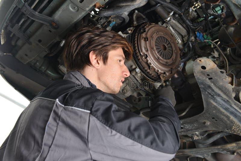 Mecánico de automóviles que trabaja debajo del coche y del embrague cambiante imagen de archivo libre de regalías