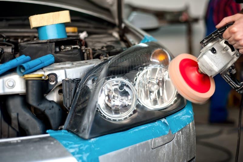 Mecánico de automóviles que trabaja en el pulido de una linterna del coche imagenes de archivo