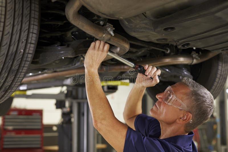 Mecánico de automóviles Working Underneath Car en garaje imágenes de archivo libres de regalías