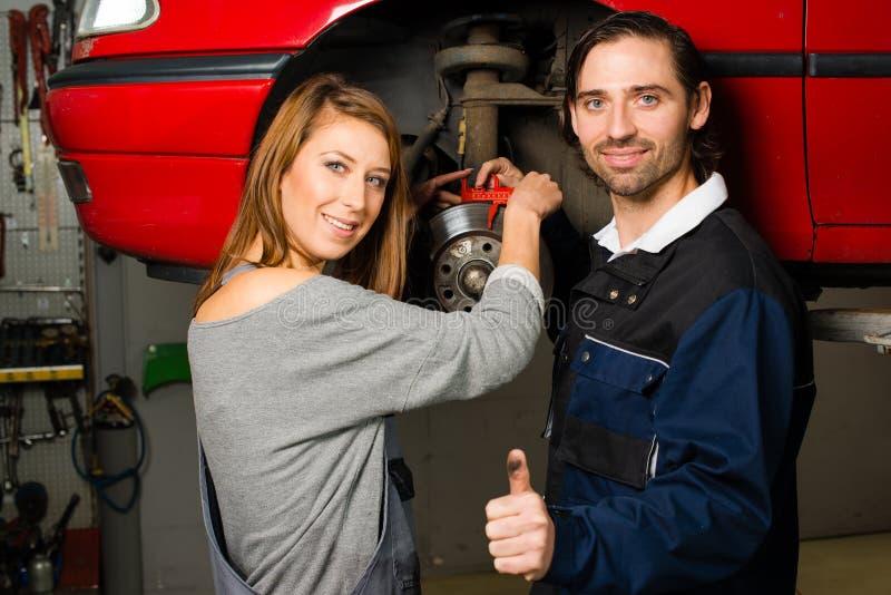Mecánico de automóviles y aprendiz femenino en garaje fotografía de archivo