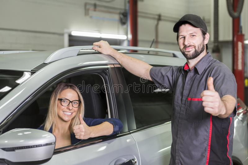 Mecánico de automóviles y cliente femenino en garaje fotos de archivo libres de regalías