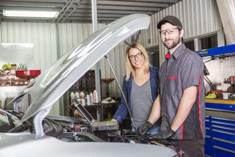 Mecánico de automóviles y cliente femenino en garaje fotos de archivo