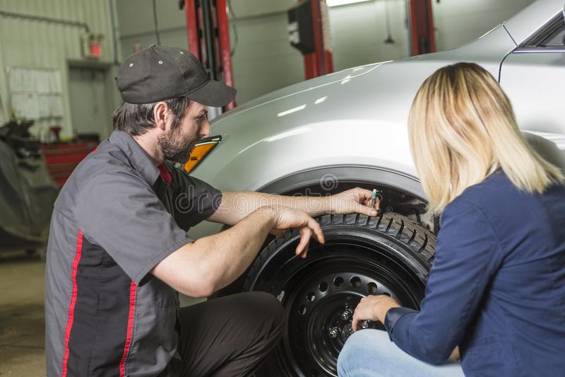 Mecánico de automóviles y cliente femenino en garaje imagen de archivo