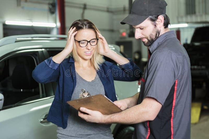 Mecánico de automóviles y cliente femenino en garaje imagenes de archivo