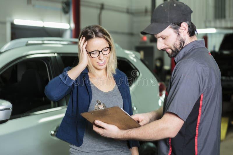 Mecánico de automóviles y cliente femenino en garaje imágenes de archivo libres de regalías