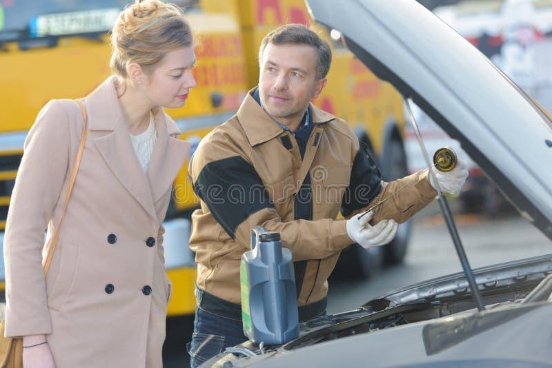 Mecánico de automóviles y cliente femenino en garaje imagen de archivo libre de regalías