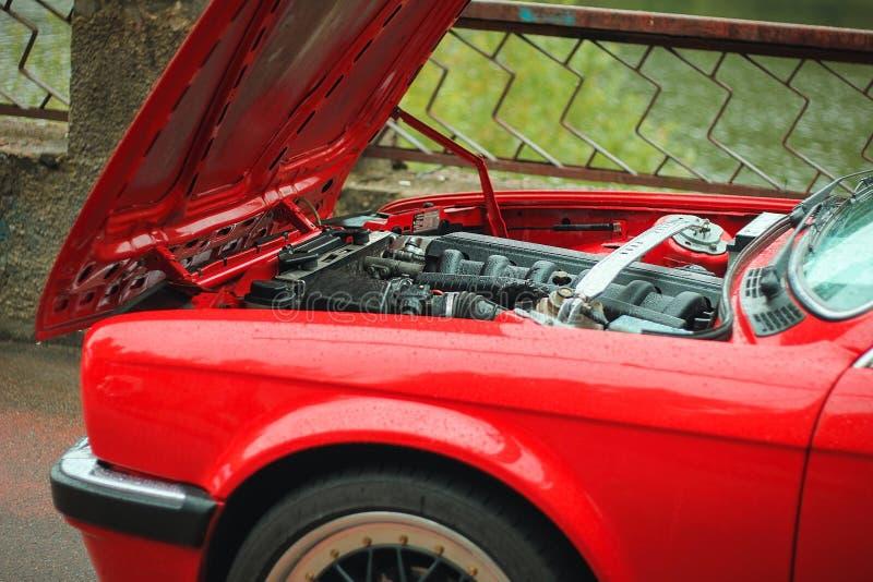 Mecánico de coche abierto de la capilla del choque de coche a la condición de control del daño foto de archivo