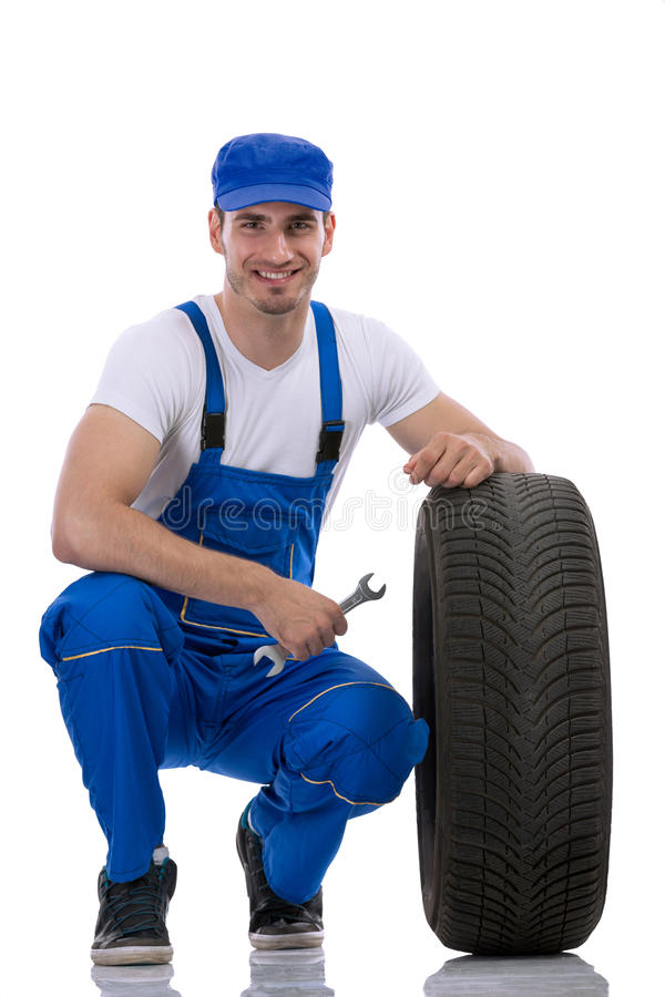 Mecánico de coche amistoso con los neumáticos fotografía de archivo