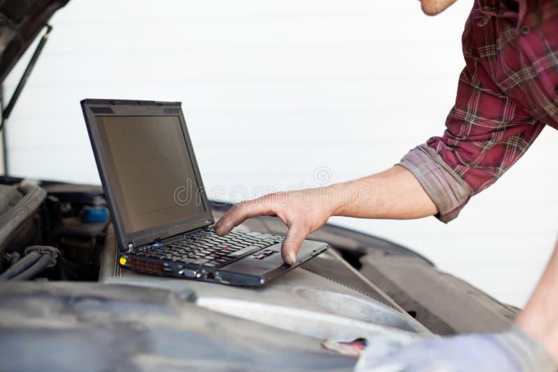 Mecánico de coche con la computadora portátil imagen de archivo libre de regalías