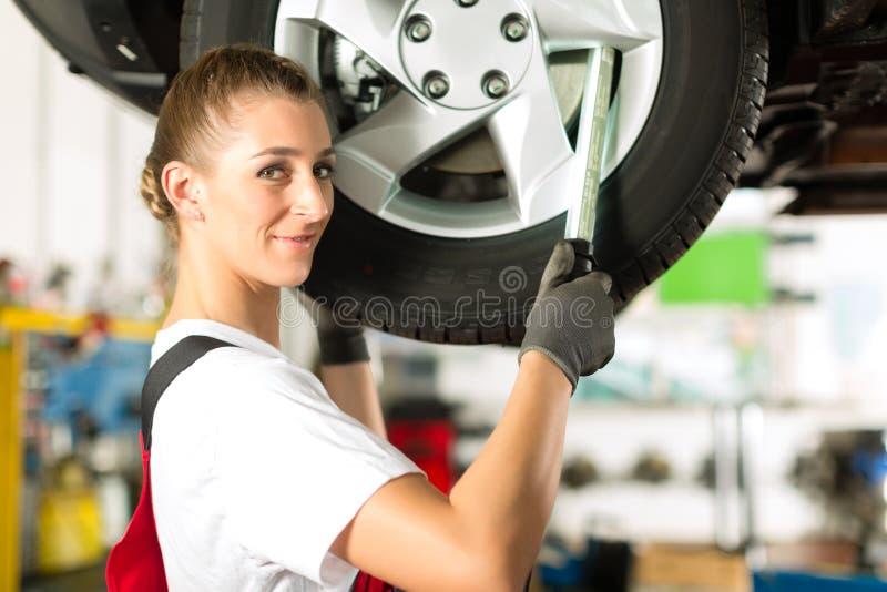Mecánico de coche de sexo femenino que trabaja en el auto levantado imagen de archivo libre de regalías