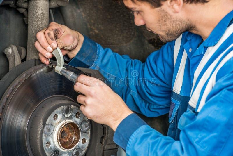 Mecánico de coche de sexo masculino Examining Brake Disc con el calibrador fotos de archivo libres de regalías