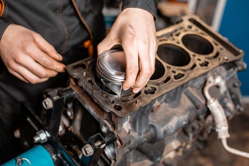 Mecánico de coche del primer que sostiene un nuevo pistón para el motor, revisión Motor en un soporte de la reparaci?n con el pis imágenes de archivo libres de regalías