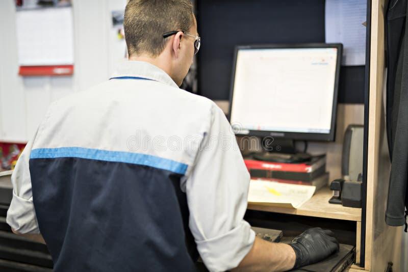 Mecánico de coche profesional que trabaja en servicio de reparación auto usando el ordenador foto de archivo libre de regalías