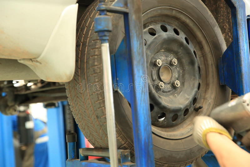 Mecánico de coche que atornilla o que desatornilla la rueda de coche imágenes de archivo libres de regalías
