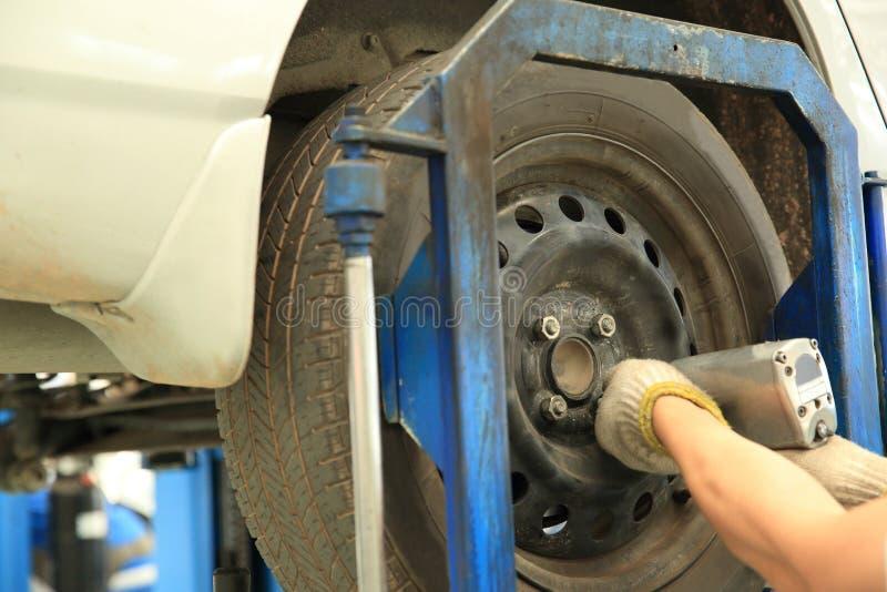 Mecánico de coche que atornilla o que desatornilla la rueda de coche foto de archivo