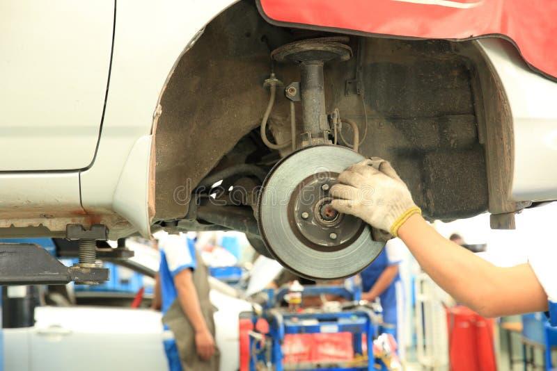 Mecánico de coche que atornilla o que desatornilla la rueda de coche fotos de archivo