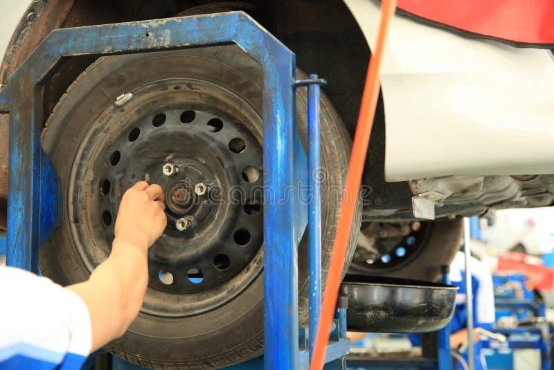 Mecánico de coche que atornilla o que desatornilla la rueda de coche fotografía de archivo libre de regalías