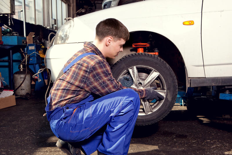 Mecánico de coche que atornilla o que desatornilla la rueda de coche del automobi levantado imagen de archivo