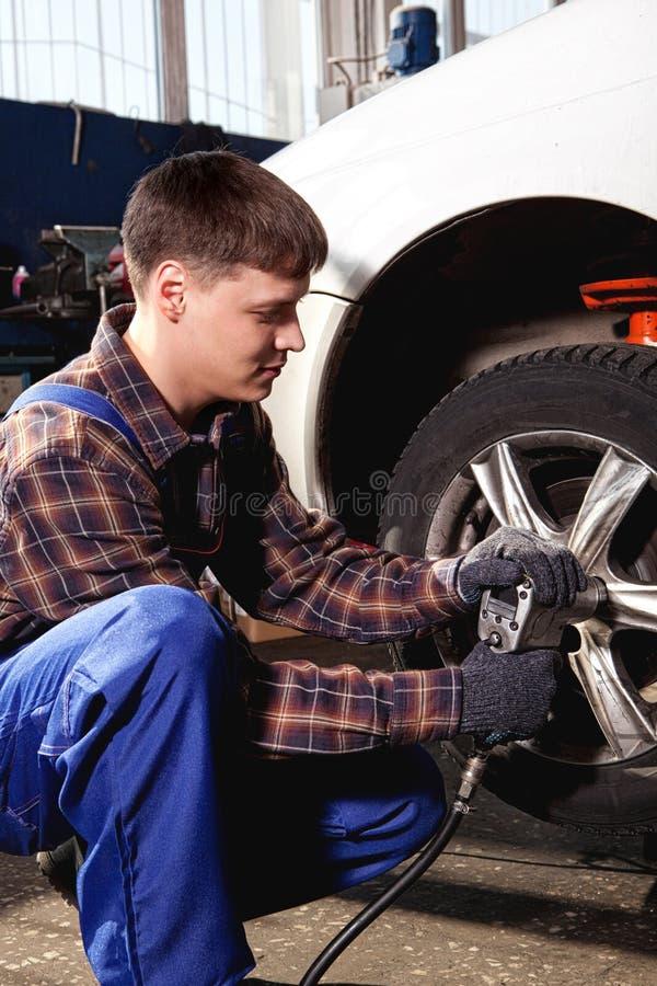 Mecánico de coche que atornilla o que desatornilla la rueda de coche del automobi levantado fotografía de archivo