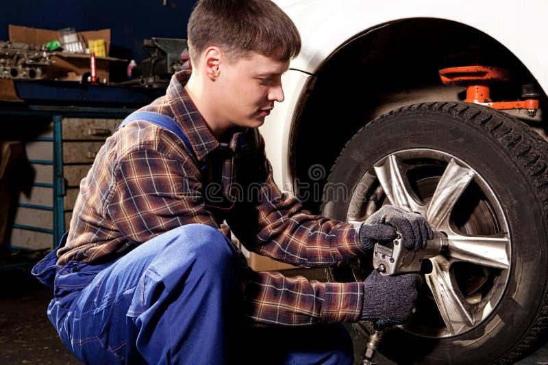 Mecánico de coche que atornilla o que desatornilla la rueda de coche del automobi levantado fotografía de archivo libre de regalías