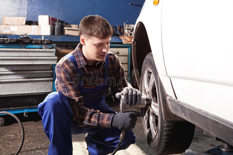 Mecánico de coche que atornilla o que desatornilla la rueda de coche del automobi levantado foto de archivo libre de regalías