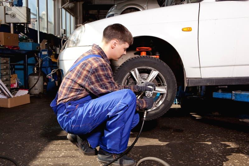 Mecánico de coche que atornilla o que desatornilla la rueda de coche del automobi levantado fotos de archivo